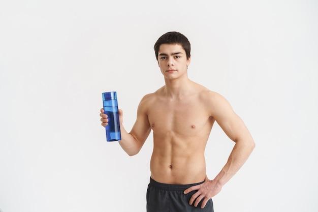 Konzentrierter fit junger hemdloser sportler, der wasserflasche über weiß zeigt
