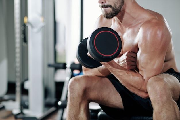 Konzentrierter fit muskulöser mann, der übung mit schwerer hantel macht, um bizeps aufzupumpen