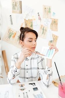 Konzentrierter frauenmodeillustrator, der am tisch sitzt.