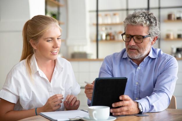 Konzentrierter freundlicher reifer männlicher mentor, der dem praktikanten die arbeitsdetails erklärt