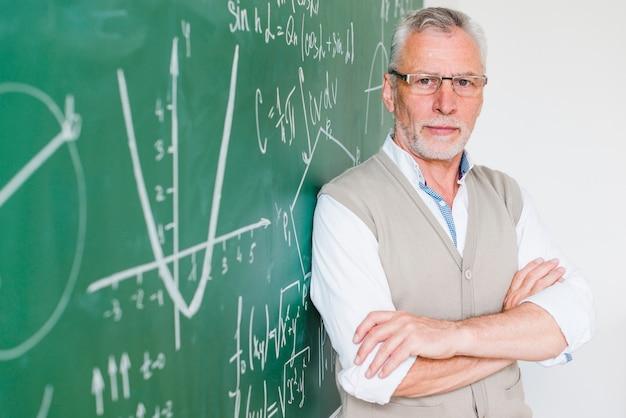 Konzentrierter gealterter mathelehrer, der auf tafel sich lehnt