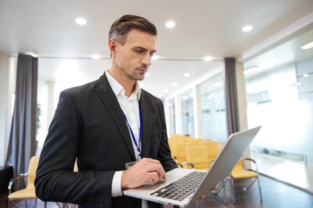 Konzentrierter geschäftsmann, der mit laptop im leeren konferenzraum arbeitet
