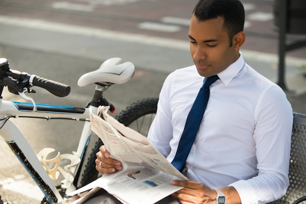 Konzentrierter geschäftsmann, der nachrichten im park liest