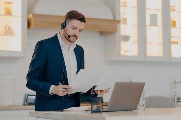 Konzentrierter geschäftsmann in anzug und headset, der papierblätter hält und informationen während eines online-meetings oder einer webkonferenz liest, büroangestellter, der in der pandemiezeit zu hause am laptop arbeitet