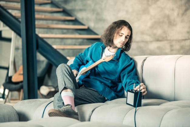 Konzentrierter gitarrist. ernster langhaariger musiker sitzt auf der couch mit gitarre auf den knien beim aufbau des verstärkers