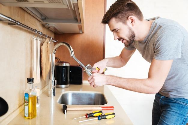 Konzentrierter, gutaussehender junger mann, der in der küche den wasserhahn mit einem schraubenschlüssel repariert Premium Fotos