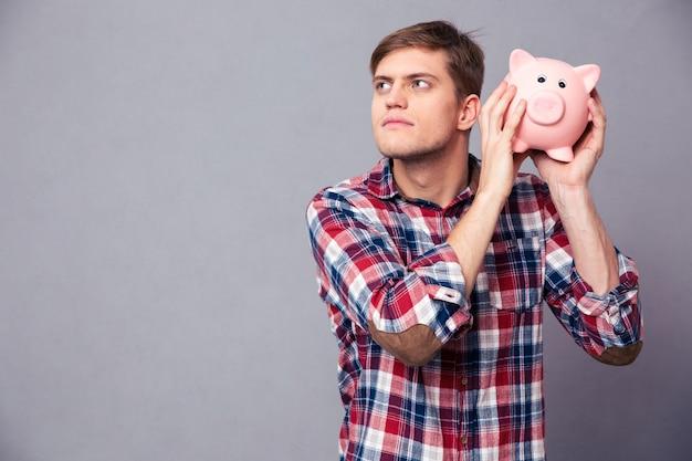 Konzentrierter gutaussehender mann im karierten hemd, das sparschwein über grauer wand hält und schüttelt