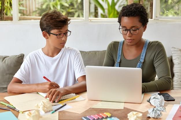 Konzentrierter hipster schreibt in notizbuchinformationen, die er von frauen hört, die nachrichten von der internet-website lesen. schöne schwarze mädchen tastaturen am laptop