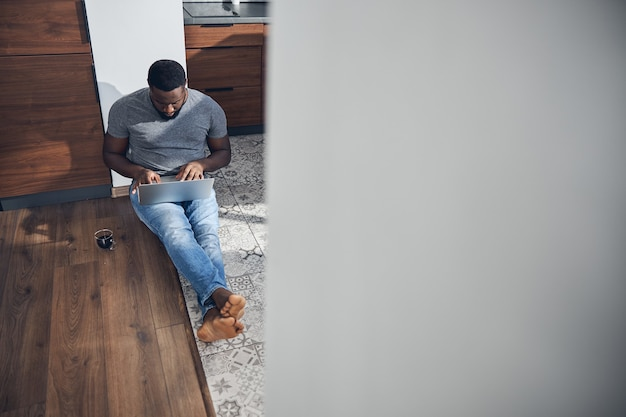 Konzentrierter internationaler mann, der auf dem boden sitzt und auf den bildschirm seines gadgets schaut, während er online chattet
