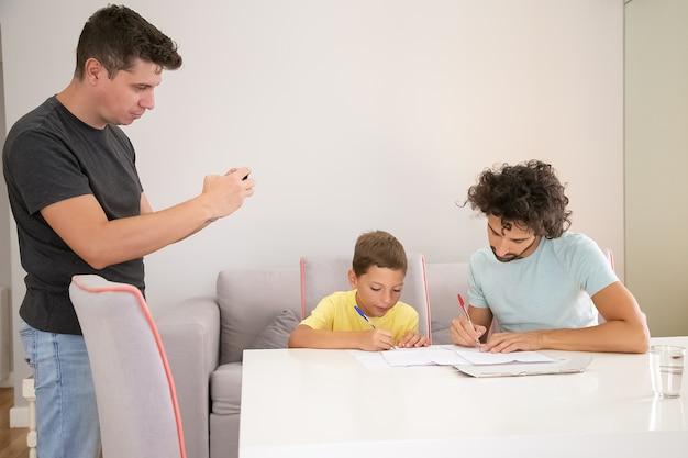 Konzentrierter junge, der mit hilfe von zwei vätern die hausaufgabe der schule erledigt und in papiere schreibt. mann, der foto seiner familie macht. konzept der familie und der schwulen eltern