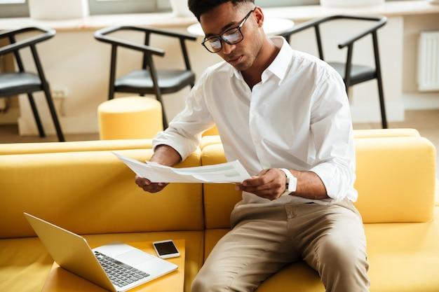 Konzentrierter junger afrikanischer mann, der coworking sitzt
