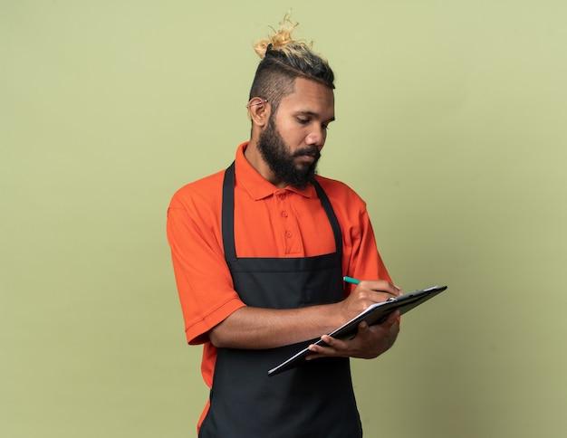 Konzentrierter junger afroamerikanischer barbier, der eine uniform trägt und die zwischenablage mit bleistift auf olivgrüner wand mit kopienraum schreibt