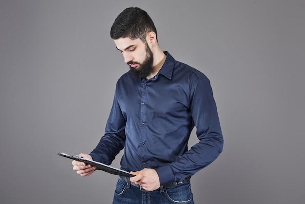 Konzentrierter junger attraktiver geschäftsmann in der blauen hemdplanung und im schreiben in der zwischenablage
