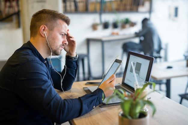 Konzentrierter junger bärtiger freiberufler, der über sein projekt am computer im café-bar-restaurant nachdenkt