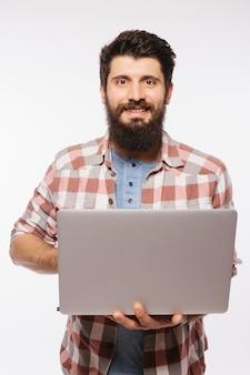 Konzentrierter junger bärtiger mann, der eine brille trägt, die im hemd unter verwendung des laptops lokalisiert über weißer wand gekleidet ist.