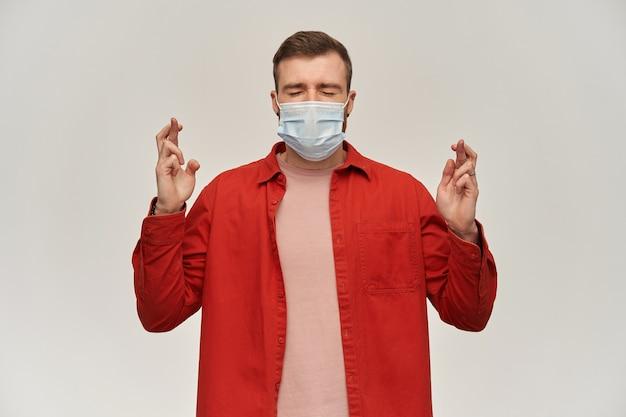 Konzentrierter junger bärtiger mann in rotem hemd und virenschutzmaske im gesicht gegen coronavirus hält die augen geschlossen und die daumen über die weiße wand gekreuzt
