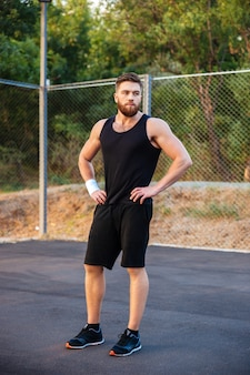 Konzentrierter junger bärtiger mann in sportkleidung, der draußen mit den händen auf den hüften steht
