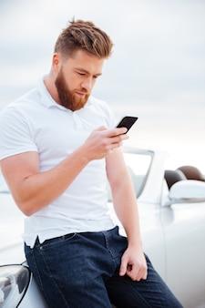 Konzentrierter junger bärtiger mann mit smartphone, das sich auf sein auto stützt