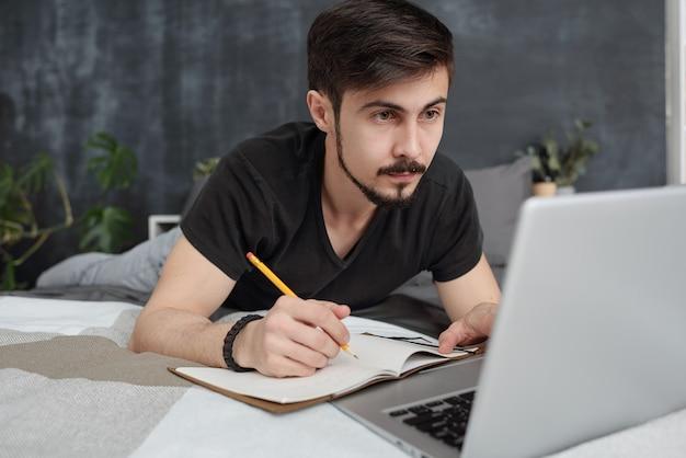 Konzentrierter junger bärtiger student, der im bett liegt und sich notizen macht, während er die vorlesung online in quarantäne hört