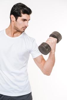 Konzentrierter junger bodybuilder mit hantel, der isoliert auf weißem hintergrund wegschaut