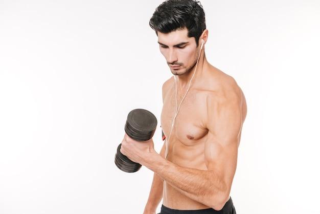 Konzentrierter junger bodybuilder mit hantel und kopfhörern isoliert auf einer weißen wand