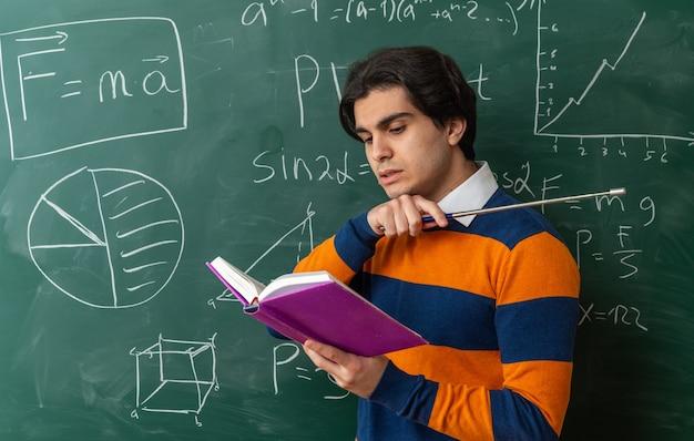 Konzentrierter junger geometrielehrer, der im profil vor der tafel im klassenzimmer steht und ein buch liest, das auf die seite zeigt