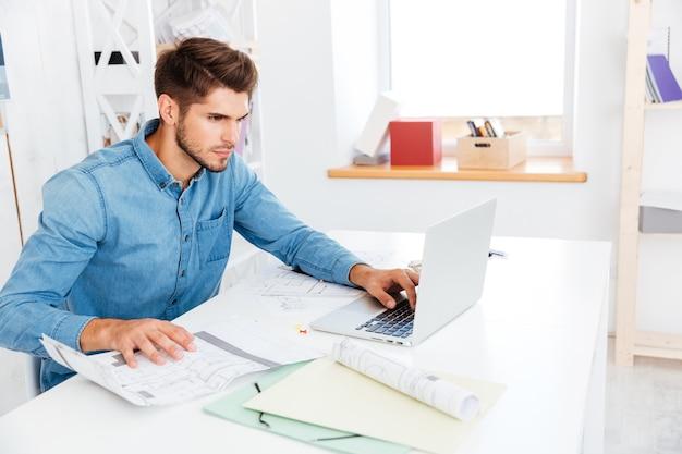 Konzentrierter junger geschäftsmann, der mit dokumenten arbeitet, während er mit laptop im büro sitzt