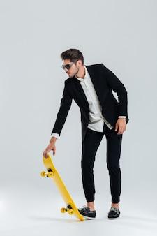 Konzentrierter junger geschäftsmann in sonnenbrille und schwarzem anzug, der ein skateboard über graue wand fahren wird