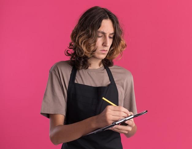 Konzentrierter junger gutaussehender barbier, der einheitliches schreiben mit bleistift auf zwischenablage trägt, isoliert auf rosa wand mit kopierraum