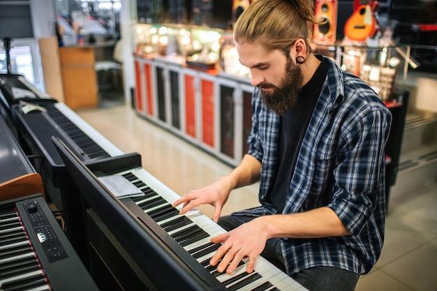 Konzentrierter junger hipster sitzt und spielt auf der tastatur. er sieht es an. guy ist alleine im zimmer.