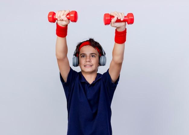 Konzentrierter junger hübscher sportlicher junge, der stirnband und armbänder und kopfhörer mit zahnspangen trägt, die hanteln erheben, die gerade lokal auf weißem hintergrund mit kopienraum suchen