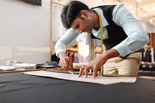 Konzentrierter junger indischer schneider, der schnittmuster auf schwarzem stoff nachzeichnet