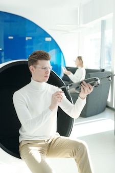 Konzentrierter junger ingenieur in intelligenten schutzbrillen, der im modernen sessel sitzt und neue drohne schafft