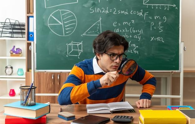Konzentrierter junger kaukasischer geometrielehrer, der eine brille trägt, die am schreibtisch mit schulwerkzeugen im klassenzimmer sitzt und die hand auf dem schreibtisch hält und durch die lupe auf die seite schaut