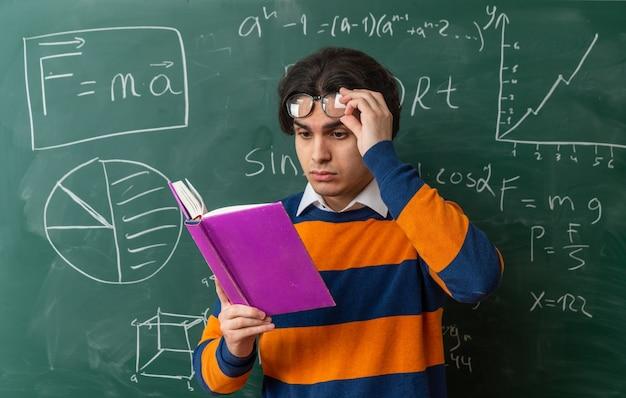 Konzentrierter junger kaukasischer geometrielehrer mit brille, der im klassenzimmer vor der tafel steht und die brille anhebt und ein buch liest