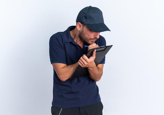 Konzentrierter junger kaukasischer lieferbote in blauer uniform und mützenschreiben mit stift auf zwischenablage