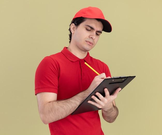 Konzentrierter junger kaukasischer liefermann in roter uniform und mütze, der in profilansicht steht und mit bleistift auf zwischenablage auf olivgrüner wand isoliert