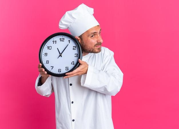 Konzentrierter junger kaukasischer männlicher koch in kochuniform und mütze, die eine uhr in der nähe des ohrs hält und auf die seite schaut, ob die uhr funktioniert oder nicht