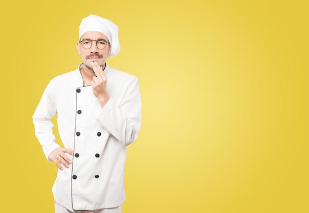 Konzentrierter junger koch, der eine geste des misstrauens macht