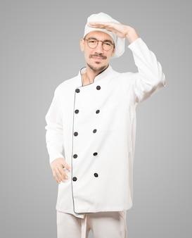 Konzentrierter junger koch mit einer geste des wegschauens