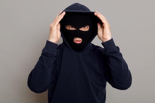 Konzentrierter junger krimineller mann in einer banditenmaske, die eine kapuze anzieht
