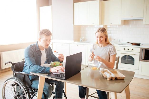 Konzentrierter junger mann auf rollstuhl, der mit laptop arbeitet und salat isst. studieren mit behinderung und inklusivität. mann mit besonderen bedürfnissen. junge frau sitzt daneben und kocht. eier brechen.