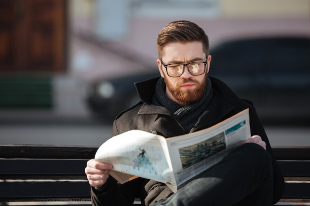 Konzentrierter junger mann, der auf bank sitzt und draußen zeitung liest
