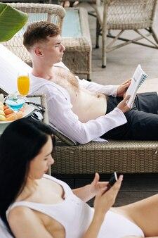 Konzentrierter junger mann, der auf der chaiselongue liegt und ein buch liest. seine freundin schreibt eine sms, wenn sie sich in der nähe ausruht