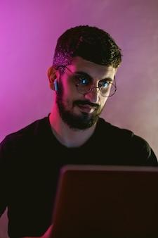 Konzentrierter junger mann, der freiberuflich an einem laptop in einem raum mit farbiger beleuchtung arbeitet.