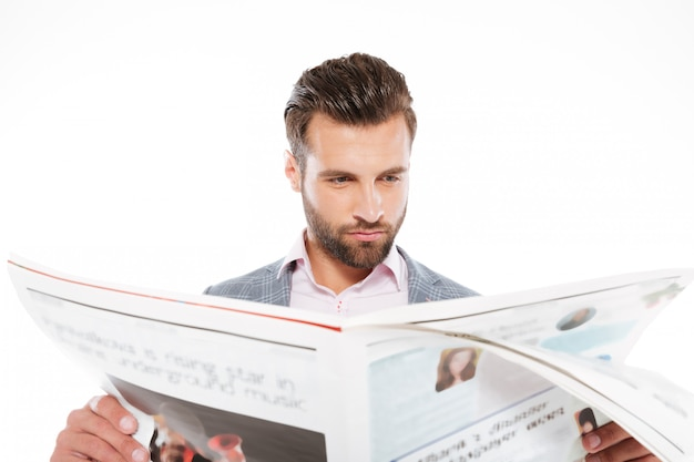 Konzentrierter junger mann, der gazette liest