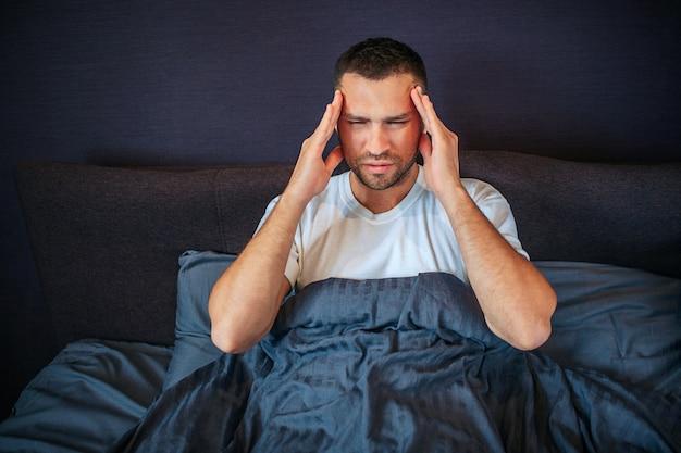 Konzentrierter junger mann hält hände neben kopf. er hält die augen geschlossen. er hat kopfschmerzen. guy leidet. er ist mit einer decke bedeckt.