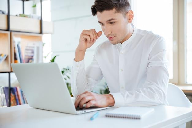Konzentrierter junger mann im weißen hemd mit laptop-computer gekleidet. coworking. laptop betrachten.