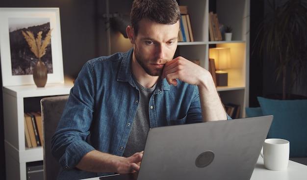 Konzentrierter junger mann mit laptop, der während der sperrung aufgrund eines virusausbruchs von zu hause aus arbeitet