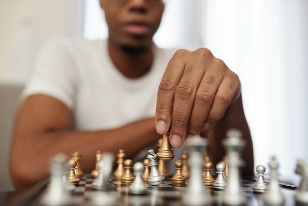 Konzentrierter junger schwarzer mann, der genießt, schach zu spielen, wenn er während der quarantäne zu hause bleibt